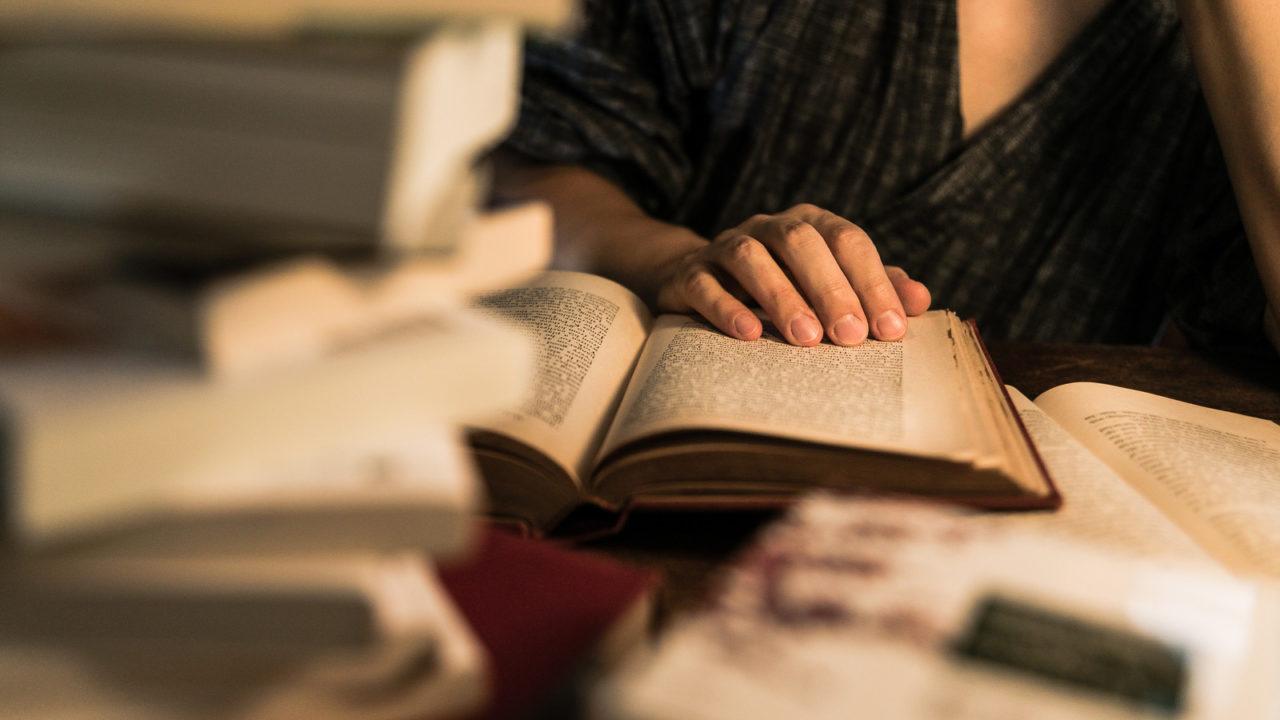 たくさんの積み上げられた本に囲まれて読書をしている人